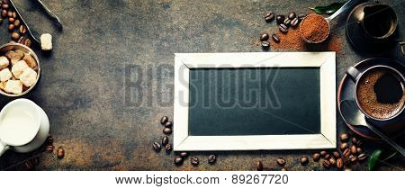 Cupof coffee and chalk board menu on dark vintage background