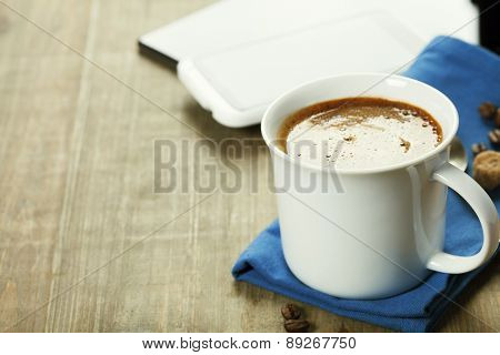 Cup of coffe with Digital tablet computer and smart phone on wooden table. Modern life and Business concept.