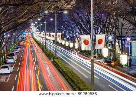 Harajuku, Tokyo, Japan traffic flows below Japanese flags at night. (Lanterns read