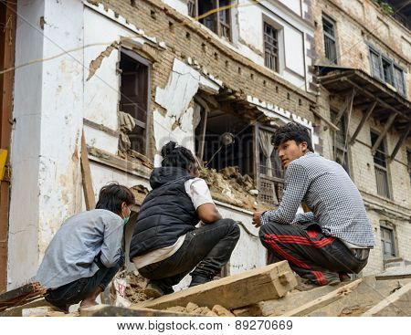 KATHMANDU, NEPAL - APRIL 26, 2015: Three young men squatting down on a pile of rubble at Durbar Square which was severly damaged after the major earthquake on 25 April 2015.