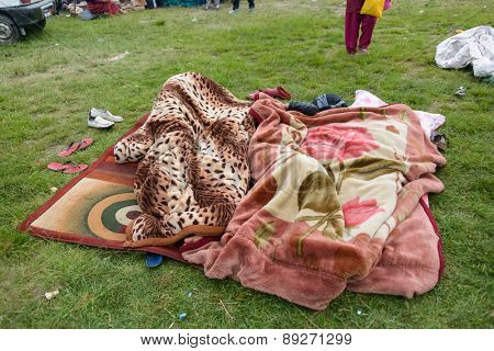 KATHMANDU, NEPAL - APRIL 26, 2015: People sleeping under blankets on an open ground at Chuchepati on the morning after the 7.8 earthquake on 25 April 2015.