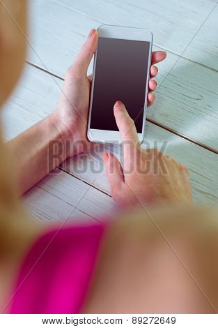 Casual woman using her smartphone at home in the living room