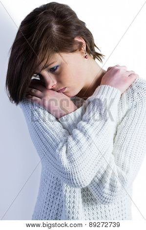 Sad pretty brunette thinking with arms crossed on white background