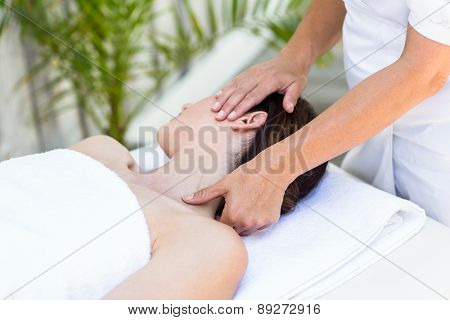 Brunette receiving neck massage at the spa