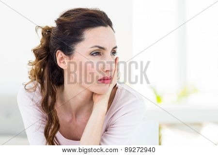 Sad brunette sitting on the couch on white background