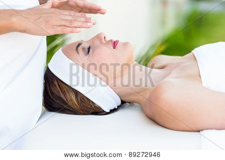 Calm woman receiving reiki treatment in the health spa