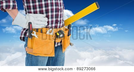 Repairman wearing tool belt while standing with hands on hips against bright blue sky with clouds