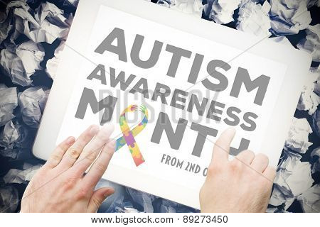 autism awareness month against hands touching tablet screen