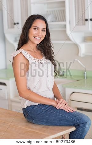 Pretty brunette sitting on table looking at camera in the kitchen