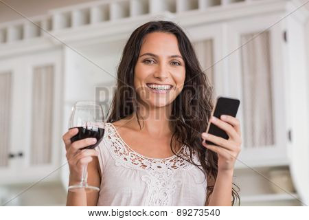 Pretty brunette using smartphone and having glass of wine in the kitchen