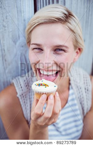 Pretty blonde woman tasting the cupcake on wooden background