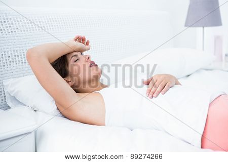 Beautiful woman with headache at home in the bedroom