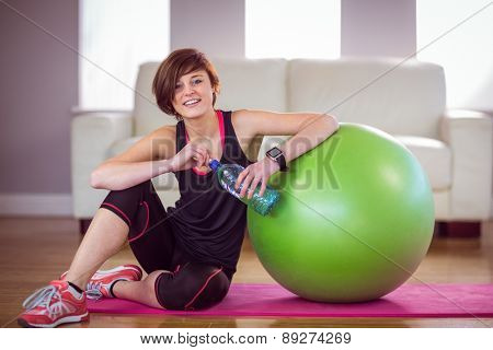 Fit woman sitting next to exercise ball at home in the living room