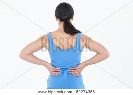 Pretty brunette suffering from back pain on white background