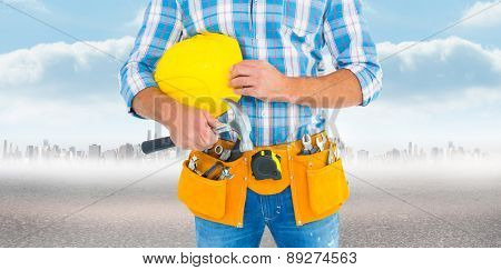 Manual worker wearing tool belt while holding hammer and helmet against city on the horizon