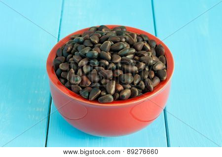 Pine nuts in a ceramic bowl on light background. Cedar nut close up