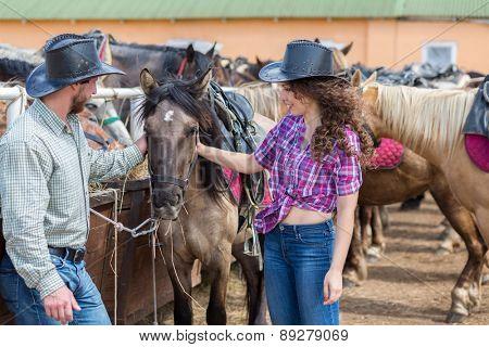cowboy couple stroking and feeding  a horse