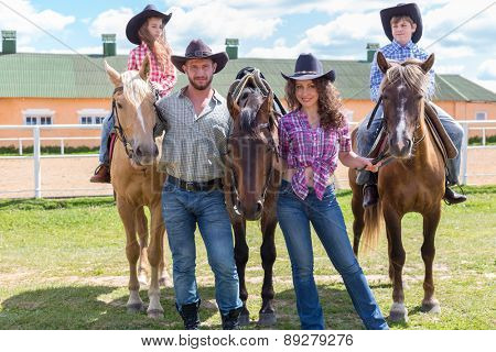cowboy family of four with horses on background of paddock