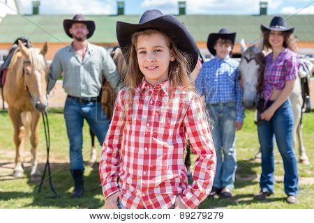 cowboy girl closeup portrait on background of her family with horses