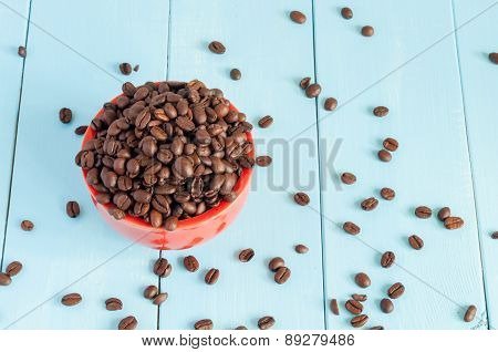 Coffee beans in red bowl on light wooden background