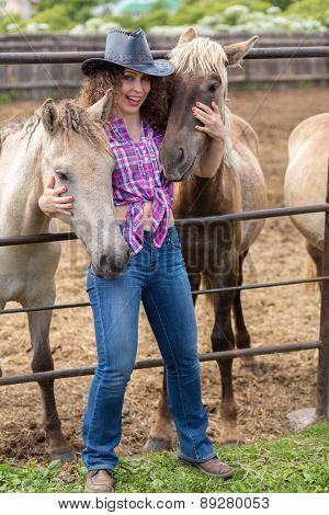 cowboy lady hugs two foals