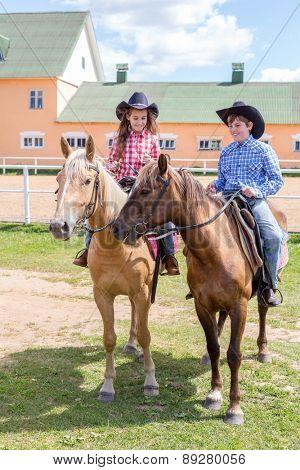 two cowboy children on horsebacks
