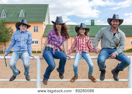 cowboy family sit on the fence of the corral