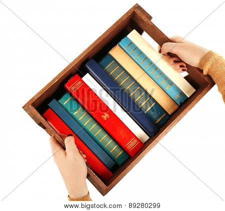 Books in wooden box in female hands isolated on white