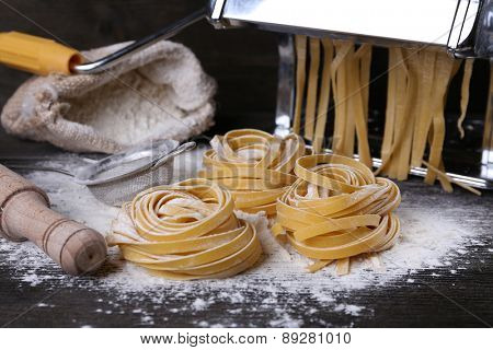 Metal pasta maker machine and ingredients for pasta on wooden background