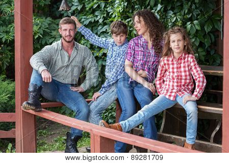 family of four sitting on terrace on background of green foliage