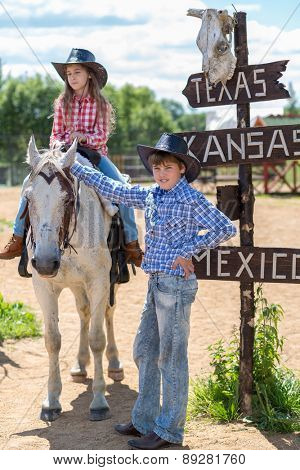 cowboy brother and sister with a signpost