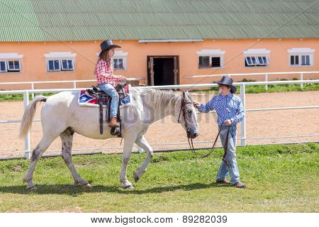 cowboy brother leads the horse of his sister by the reins