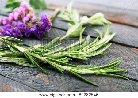 Green herbs and leaves on wooden  table, closeup