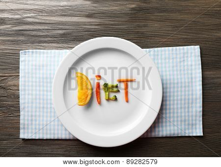 Word DIET made of sliced vegetables in plate on wooden table, top view