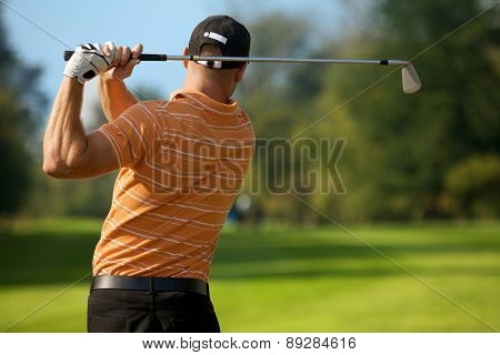 Young man swinging golf club, rear view