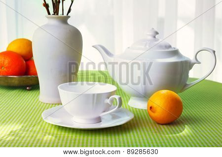 Willow twigs, teapot, cups and citrus on table on curtains background