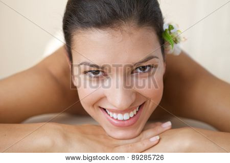 Close-up of cheerful young woman relaxing on massage table