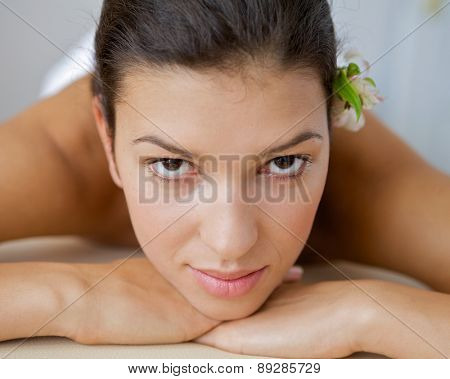 Close-up of young woman relaxing on massage table