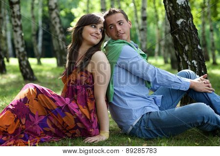 Young couple sitting back to back in park