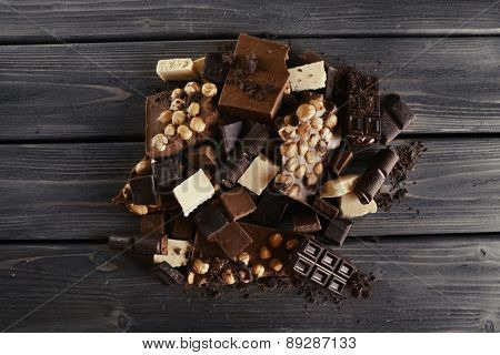 Set of chocolate with hazelnut on wooden table, top view