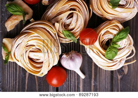 Raw homemade pasta with cheese and vegetables on wooden background