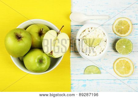 Apples, cottage cheese and lemons on wooden table top view