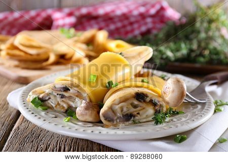 Pancakes with creamy mushrooms in plate on wooden table, closeup