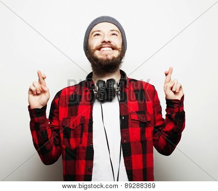 life style and people concept:Waiting for special moment. Portrait of young bearded man in shirt keeping fingers while standing against white background. Hipster style and positive emotions.