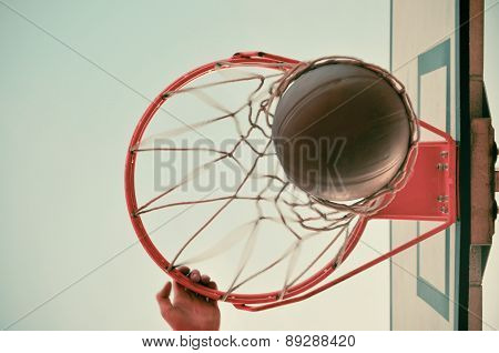 A Man Dunking A Basketball Through A Net With One Hand