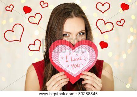 Smiling girl holding Valentines card on festive background