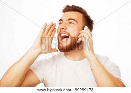 life style, happiness and people concept: young bearded man holding hand near mouth and shouting while standing against white background