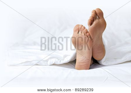 Person's foot in bed