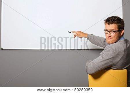 Portrait of businessman pointing at whiteboard and making face in office