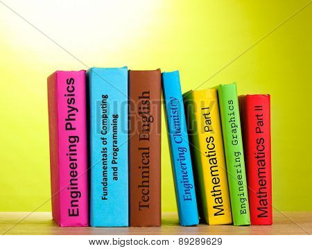 Colorful books on table on color background